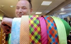 Sarasportin kauppias Martti Salonen sanoo, että muotitietoinen pukeutuu tänä keväänä värikkäästi. Mukavan piristeen asuunsa saa vaikkapa kirjavalla kravatilla. Kuva: Kati Uusitalo