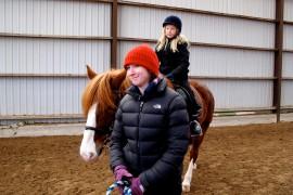 Loimihaan laskiaisriehassa ohjemassa oli talutusratsastusta maneesissa, hevosajelua radalla ja pulkkaratsastusta kentällä. Maren Nie talutti, kun Elsa Karppi, 9, ratsasti Hippula-hevosella. Isovanhempiensa ja serkkunsa kanssa tapahtumaan tullut Elsa aikoi suunnata iltapäivällä vielä laskiaisen pulkkamäkeen. Kuva: Kiti Salonen