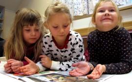 Ta-daa, tässä se on, lehden kiinnostavin juttu nimittäin, Josefiina, Helmi ja Milana näyttävät. Se kertoo tietenkin hevosista. Kuva: Kati Uusitalo