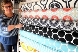 Anne-Mari Laaksonen AnneMari´s -liikkeestä kertoo, että keväisin ihmiset innostuvat hankkimaan iloisia ja värikkäitä sisustuskankaita, joista voi valmistaa verhoja ja tyynynpäällisiä. Kuva: Marianne Rovio