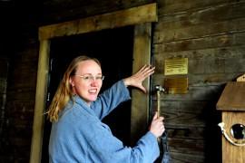 Kristiina Heinonen naulasi palkintolaattaa savusaunan seinään. Kuva: Ari Reinikainen