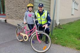 Elviira Luontomaa sai koulupoliisi Pekka Mäkelältä ohjeet siihen, miten katu ylitetään pyörän kanssa turvallisesti. Kuva: Tiina Naula