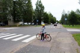 Ennen kadun ylitystä pyöräilijän pitää hypätä pois pyörän selästä ja katsoa tarkkaan molempiin suuntiin, ettei autoja tai muita ajoneuvoja ole tulossa. Elviira Luontomaa näyttää mallia. Kuva: Tiina Naula