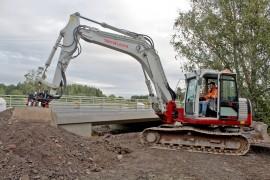 Kaivinkoneenkuljettaja Esa Lähteenmäki ahkeroi Hanhijoen sillan uusimistöissä, jotka ovat jo loppusuoralla. Kuva: Tiina Naula