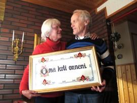 Onni on oma koti, mutta etenkin rakkaus ja läheiset, Sirpa ja Jaakko Kallionpää tuumivat. Sirpan itse kirjailema taulu on kodissa kunniapaikalla. Kuva: Kati Uusitalo