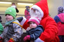 Almo, 3, ja Aila, 2, Kingsley pääsivät joulunavauksessa joulupukin polvelle. Kuva: Kiti Salonen