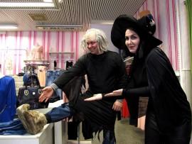 """Prättäkitti-päivän noidat Martti Koskinen ja Kaisa Koivisto esittelivät noitamaiseen tyyliin uusinta uutta jalkinemuotia kenkiä ja muotia myyvässä Todayssa. Kauppias kiitteli, että lapsiperheitä oli liikkeellä ja edelleen pukeutuneet """"noidat"""" ja kauppojen panostaminen päivään kiinnostaa asiakkaita. Hän tosin toivo, että useampi kauppa olisi tempauksessa mukana. Kuva: Kati Uusitalo"""