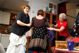 Eila Nummila, Mirja Honkanen ja Kaija Joensuu huomaavat, että mekon selästä puuttuu kangasta. Kuva: Anu Salo