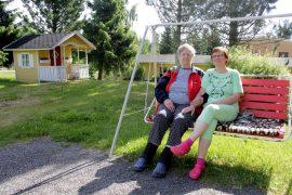 Eila Jokinen ja Ritva Kolinkanta istahtavat mielellään aina välillä keinuun ihailemaan kaunista pihaa ja jutustelemaan naapureiden kanssa. Kuva: Tiina Naula