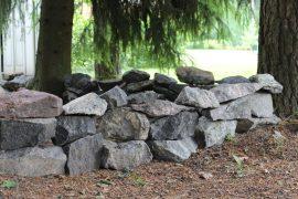 Tontti rajautuu pieneen metsikköön. Metsän reunaan on rakenteilla kiviaita. (Kuva: Kiti Salonen)