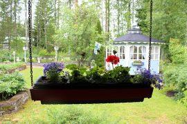 Autokatoksen reunasta roikkuu kukkalaatikoita. Kuva: Emilia Voltti