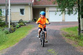 Lapsenlapsi Antti Ristanen nauttii isovanhempiensa rauhallisesta pihasta, jolla saa pyöräillä ilman huolta autoista. Kuva: Siiri Jumppanen