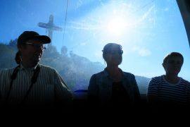 Esko Tiiri, Liisa Kivinen ja Hannele Tiiri matkaavat yläilmoihin kaapelihississä Skopjessa katsastamaan muistomerkkiä.