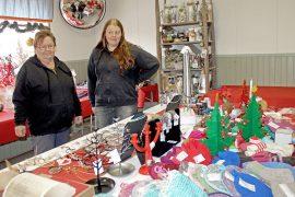 Mellilän kyläyhdistyksen Eila Suuniitty ja Taru Nurmi esittelevät upeita käsitöitä ja joulukoristeita, joita Mellilän Joulupuodissa on tarjolla. Kuva: Marianne Rovio