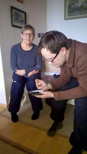 Digitalisaatio muutti kaiken. Uusi teknologia tuli lyhyessä ajassa jokaisen kansalaisen jokapäiväiseen elämänpiiriin. Myös varttuneen väen oli pakko oppia. Tietotekniikan oppimisessa nuoremmat opettivat vanhempiaan. Uusien asioiden oppiminen on ikääntyneenä vaikeampaa ja hitaampaa. Kuvassa nuorempi polvi opastaa vanhempaa älypuhelimen käytössä. Kuva helmikuu 2017. Jukka Ristimäki.
