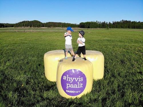 Sisu Silvennoinen ja Rasmus Rauhala poseeraavat keltaisten paalien mainoskuvassa.